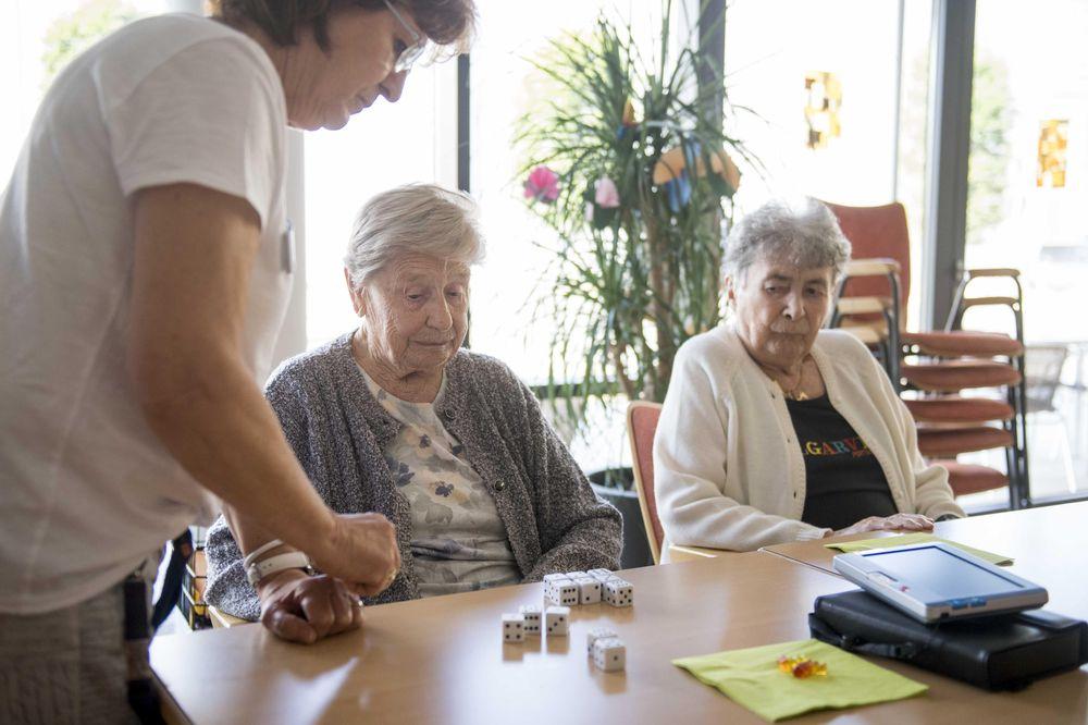 Eine Betreuungsassistentin spielt mit zwei Damen ein Würfelspiel.