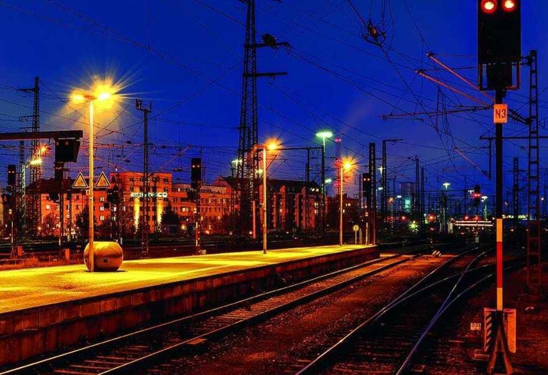 Ein Bahnsteig am Nürnberger Bahnhof in der Dämmerung. Die Straßenlaternen taucht den Bahnsteig in warmes Licht.
