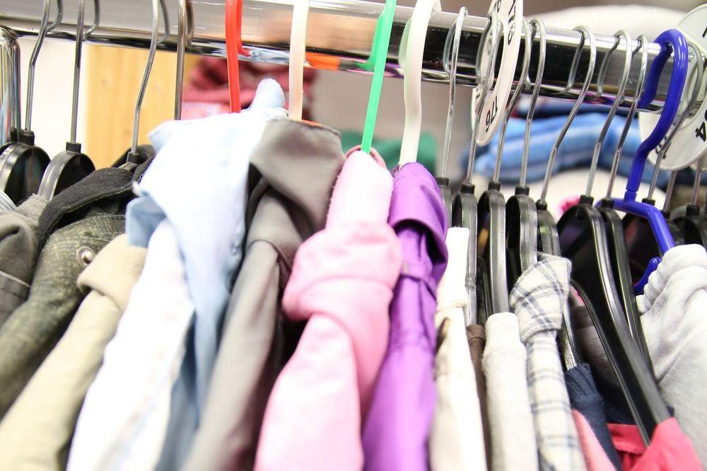 Dünne Jacken und Hemden hängen auf bunten Bügeln an einer Kleiderstange.