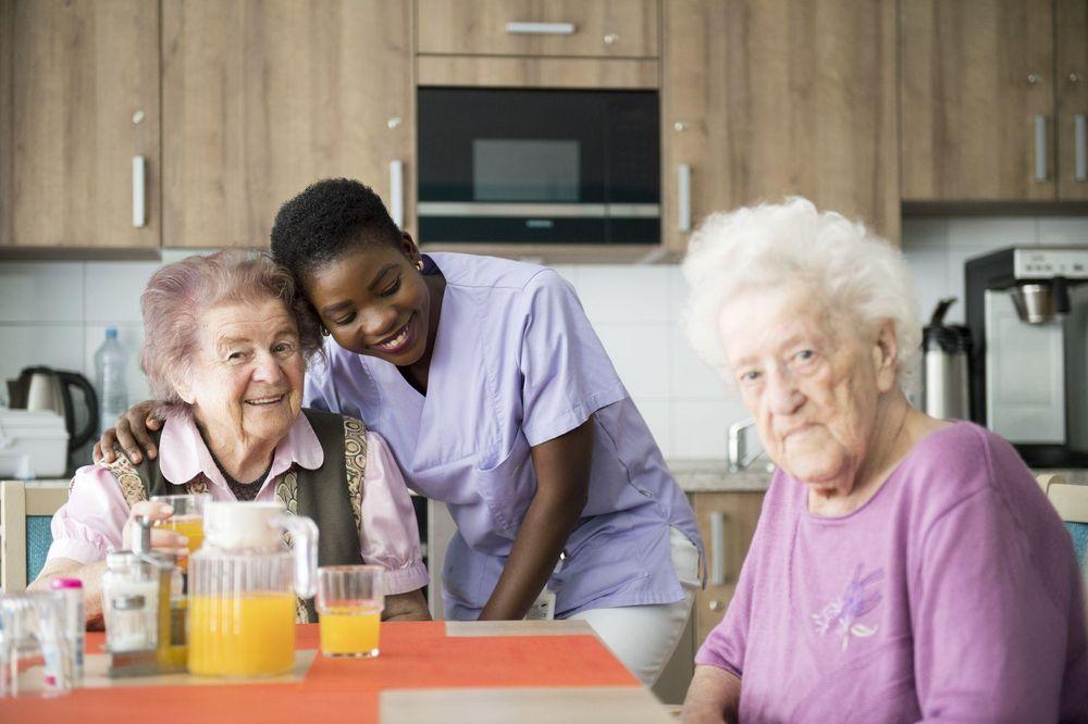 Eine Pflegerin steht bei zwei älteren Damen, die an einem Tisch sitzen.