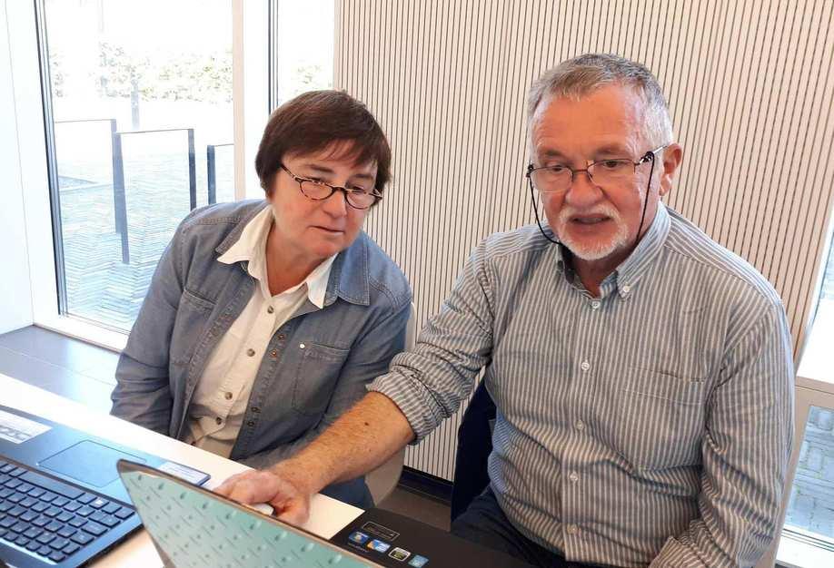 Eine ältere Frau und ein älterer Mann sitzen nebeneinander vor zwei Laptops. Sie schaut ihm über die Schulter auf seinen Bildschirm.