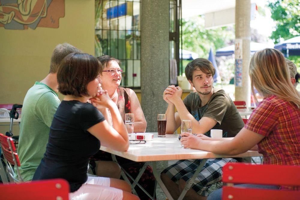 Fünf Personen sitzen in einem Café