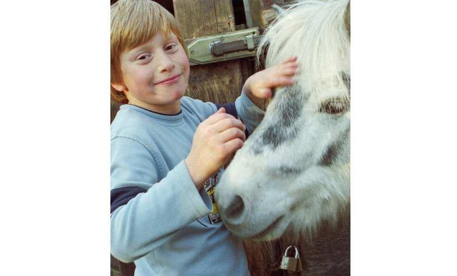 Kind streichelt Pony