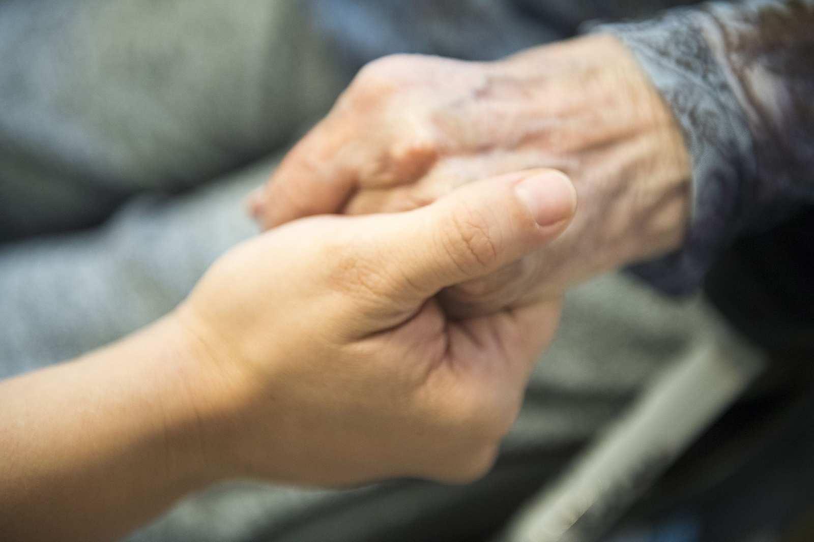 Eine junge Hand und eine alte Hand halten sich.