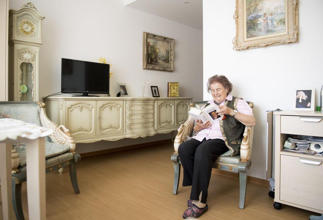 Eine Dame sitzt in ihrem mit persönlichen Gegenständen eingerichteten Einzelzimmer und liest ein Buch.