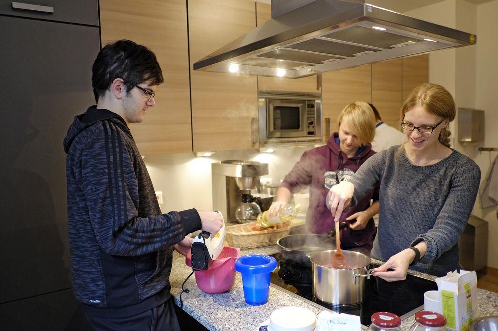 Drei Personen kochen zusammen in einer Küche.