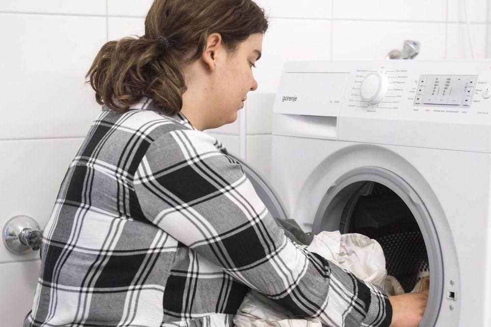 Eine Frau die Wäsche in die Waschmaschine tut