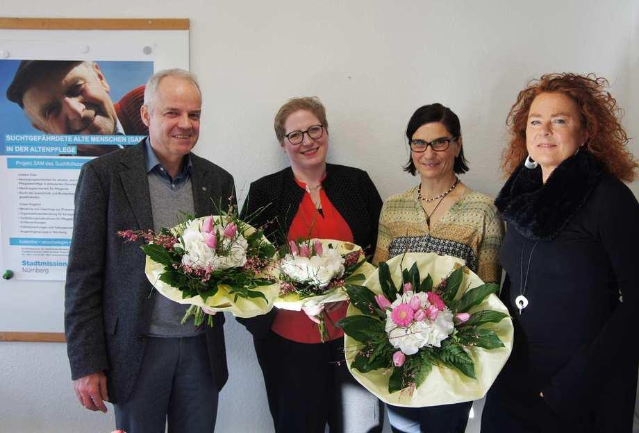 """Vor dem Projektplakat von """"SAM"""" stehen ein Herr und drei Frauen nebeneinander und lächeln. Sie haben Blumensträuße in ihren Händen."""