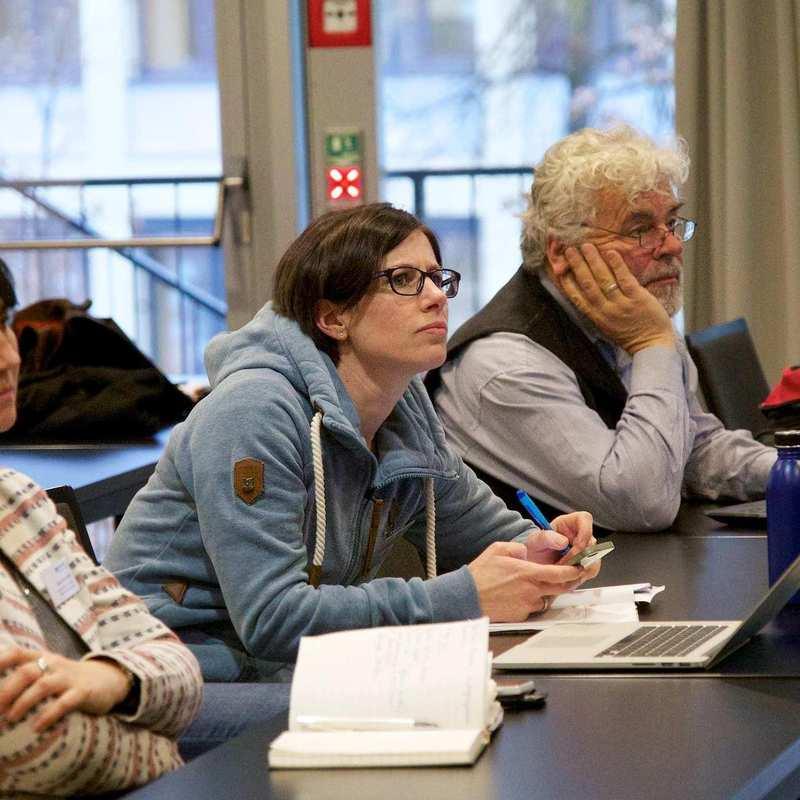 Zwei Frauen und ein Mann unterschiedlichen Alters sitzen an einem Konferenztisch.