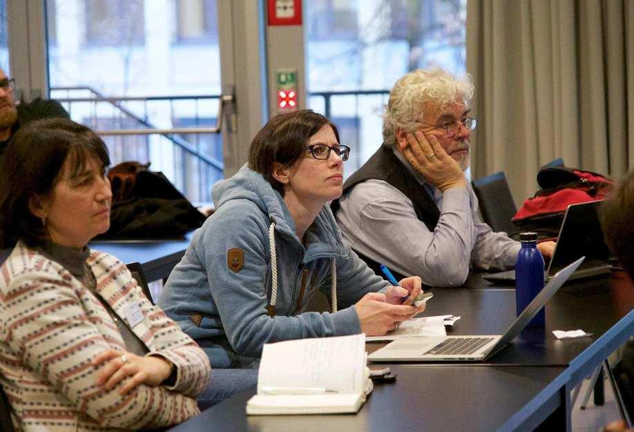 Zwei Frauen und ein Mann unterschiedlichen Alters sitzen in einer Reihe an einem Konferenztisch.