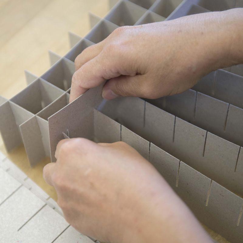 Zwei Hände stecken Kartons zusammen.