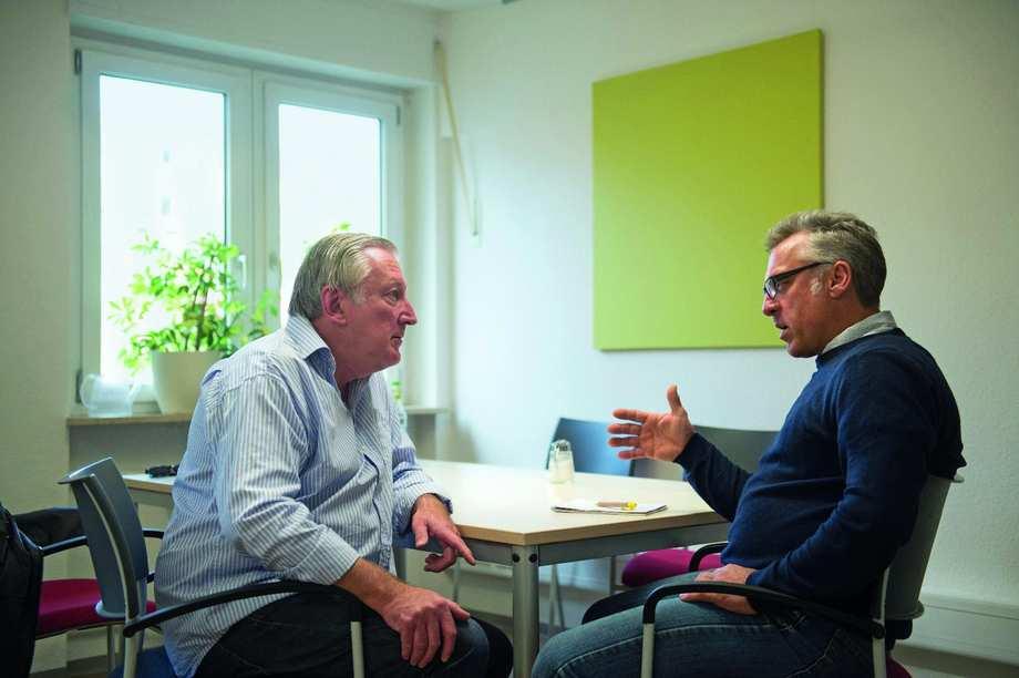 Zwei Männer sitzen sich an einem Tisch gegenüber und unterhalten sich.
