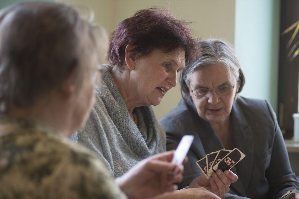"""Drei Frauen spielen das Kartenspiel """"Uno""""."""
