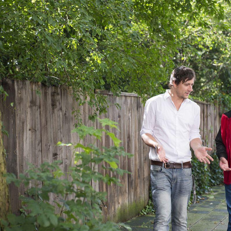 Zwei Männer laufen einen Weg entlang und unterhalten sich.
