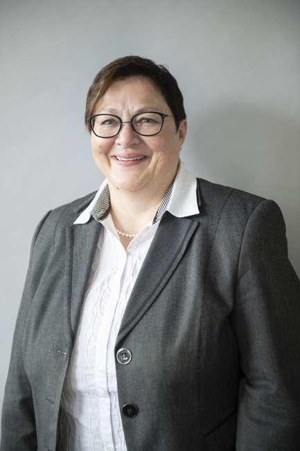 Eine lächelnde Frau mit Brille. Sie trägt eine weiße Bluse mit grauem Blazer.