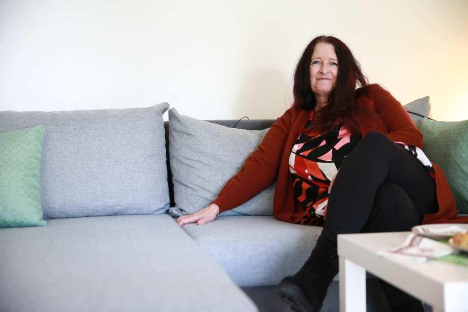 Eine Frau mit langen schwarzen Haaren sitzt auf einer grauen Couch. Sie lächelt.