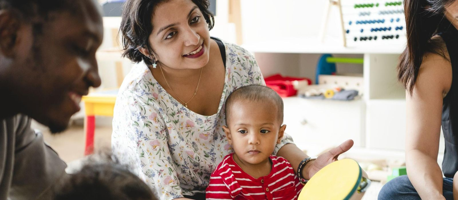 Eine Mutter sitzt mit ihrem Kind auf dem Boden und spielt auf einer Trommel. Um sie herum sitzen noch weitere Eltern mit ihren Kindern.