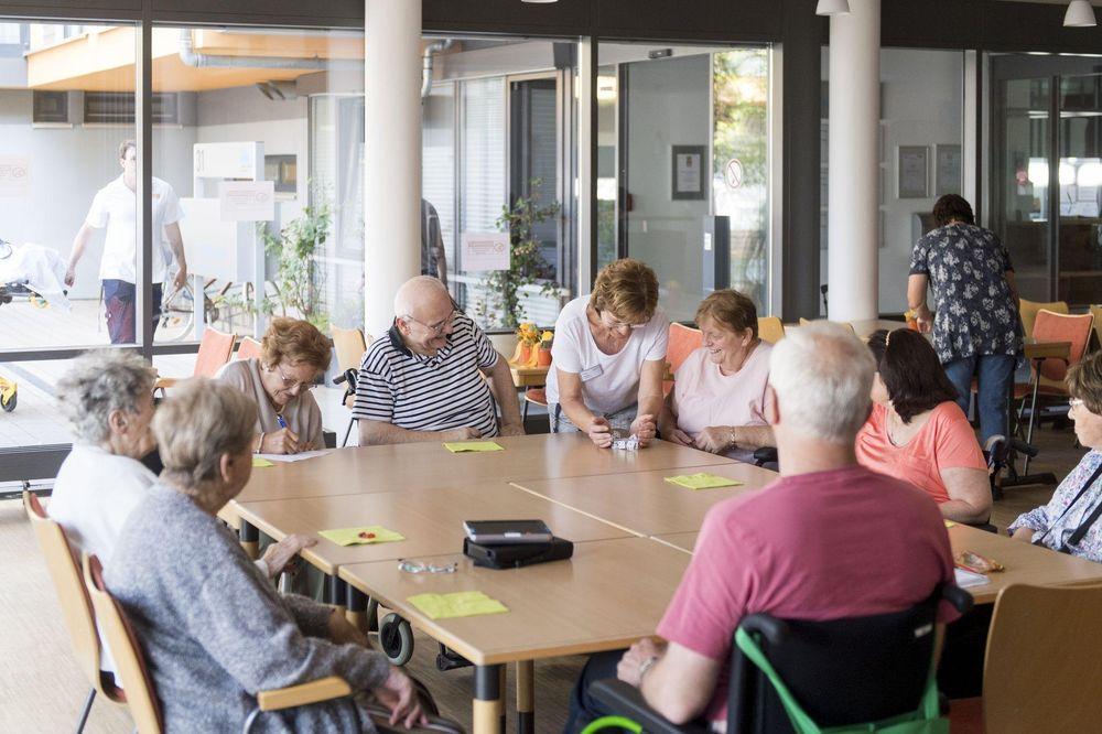 Acht Bewohner*innen des Pflegeheims spielen mit einer Mitarbeitenden an einem großen Tisch Kniffel.