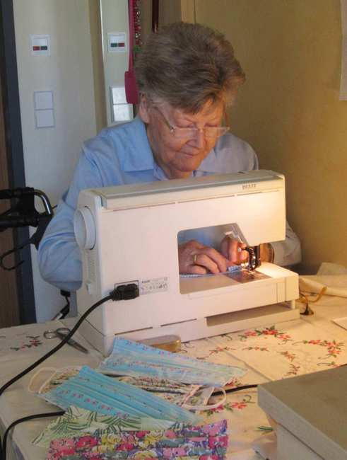 Eine alte Dame mit grauen kurzen Haaren sitzt konzentriert hinter einer Nähmaschine.