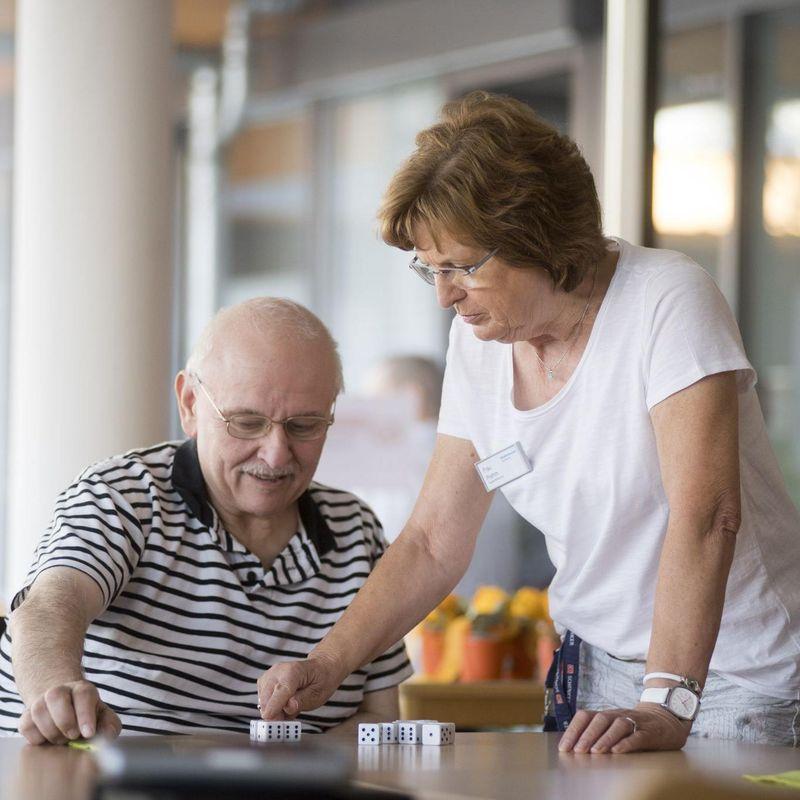 Eine Mitarbeiterin spielt mit einem Bewohner im Rollstuhl Kniffel.