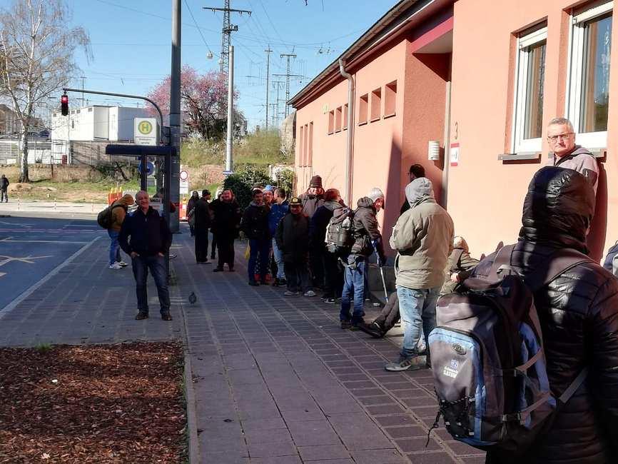 Vor der Ökumenischen Wärmestube: Auf dem Bürgersteig steht eine lange Schlange von Menschen.