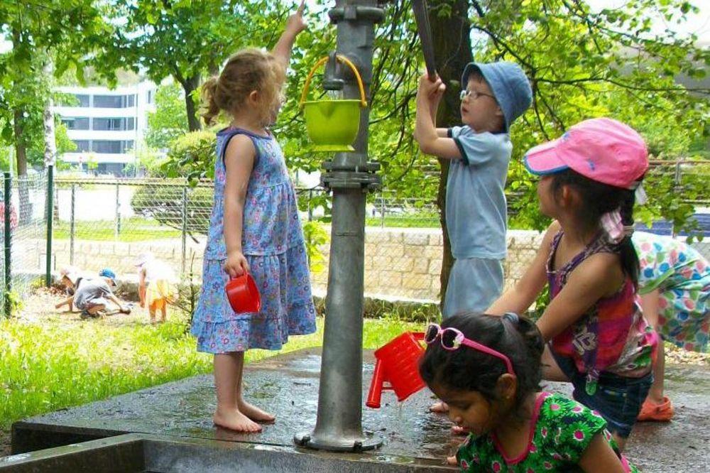 Vier Kinder spielen an einem Wasserspielplatz bzw. Brunnen.