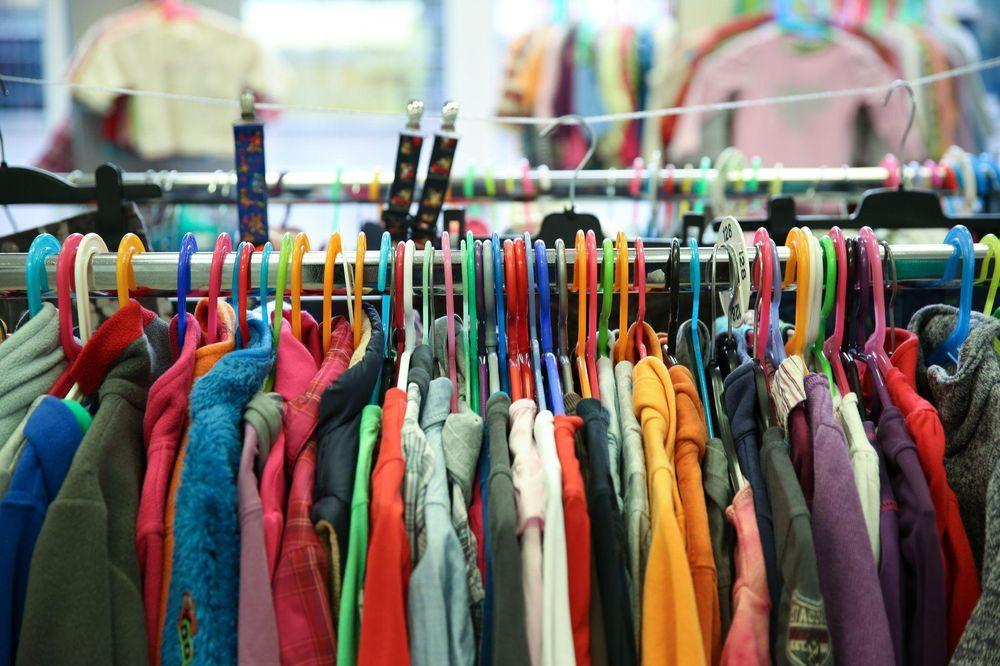 Eine Kleiderstange mit vielen bunten Bügeln und bunter Kleidung