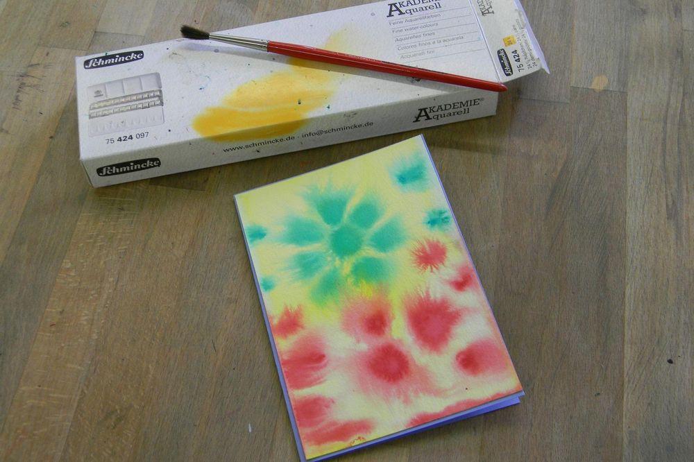 Ein mit Wasserfarben gemaltes Bild und ein Pinsel, der auf einem Karton liegt