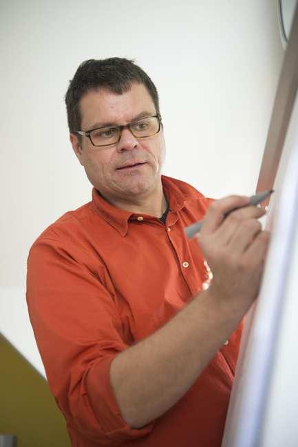 Ein Mann steht mit einem Stift an einer Flipchart.