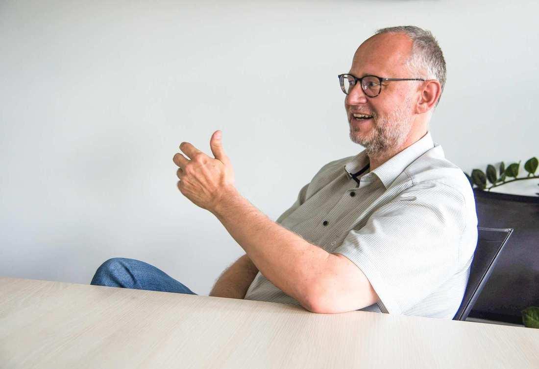 Ein Mann mit Brille, grau melierter Stoppelfrisur und Stoppelbart. Er trägt ein graues Hemd.