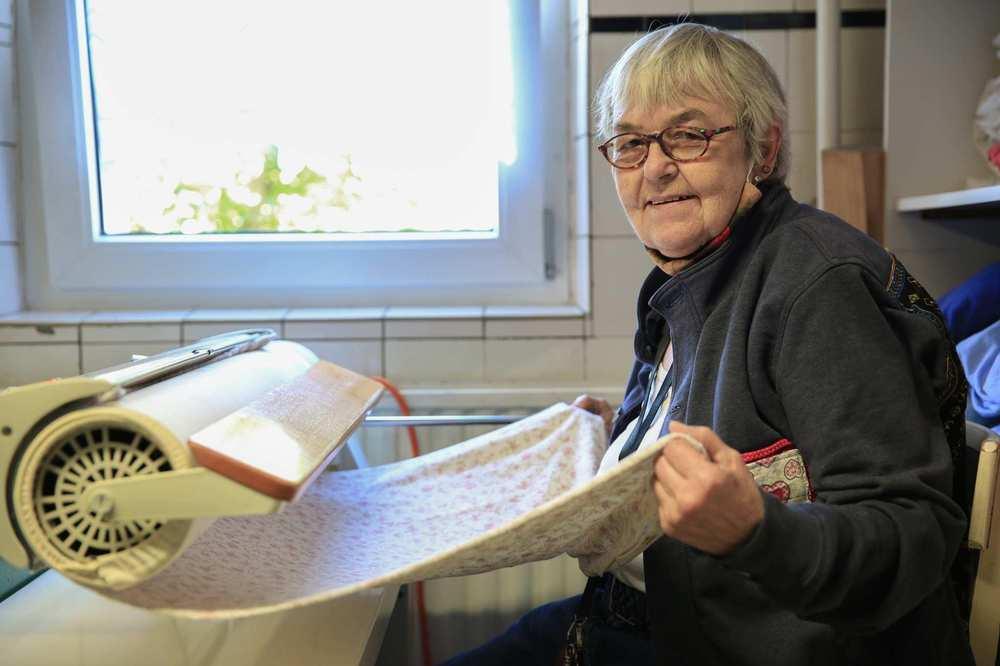 Eine Bewohnerin im Hauswirtschaftsraum bügelt Wäsche an der Bügelmaschine