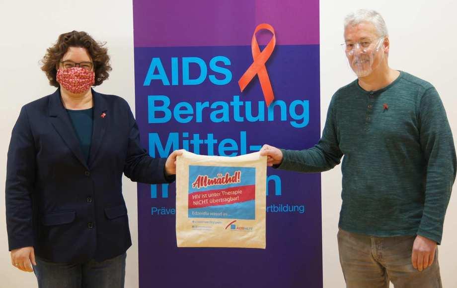 Eine Frau und ein Mann stehen links und rechts neben dem Roll-Up der AIDS-Beratung. Sie tragen Masken.