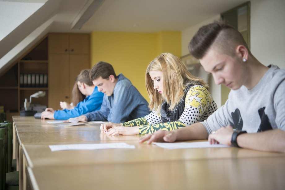 Vier Jugendliche sitzen mit Arbeitsblättern an einer Tischreihe.