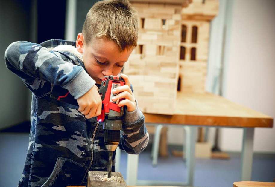 Ein Junge bohrt konzentriert mit einem neuen Holzbohrer an einem Holzklotz