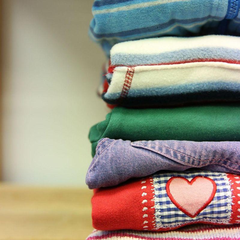 Ein Stapel zusammengelegter bunter Kleider auf einem Regal
