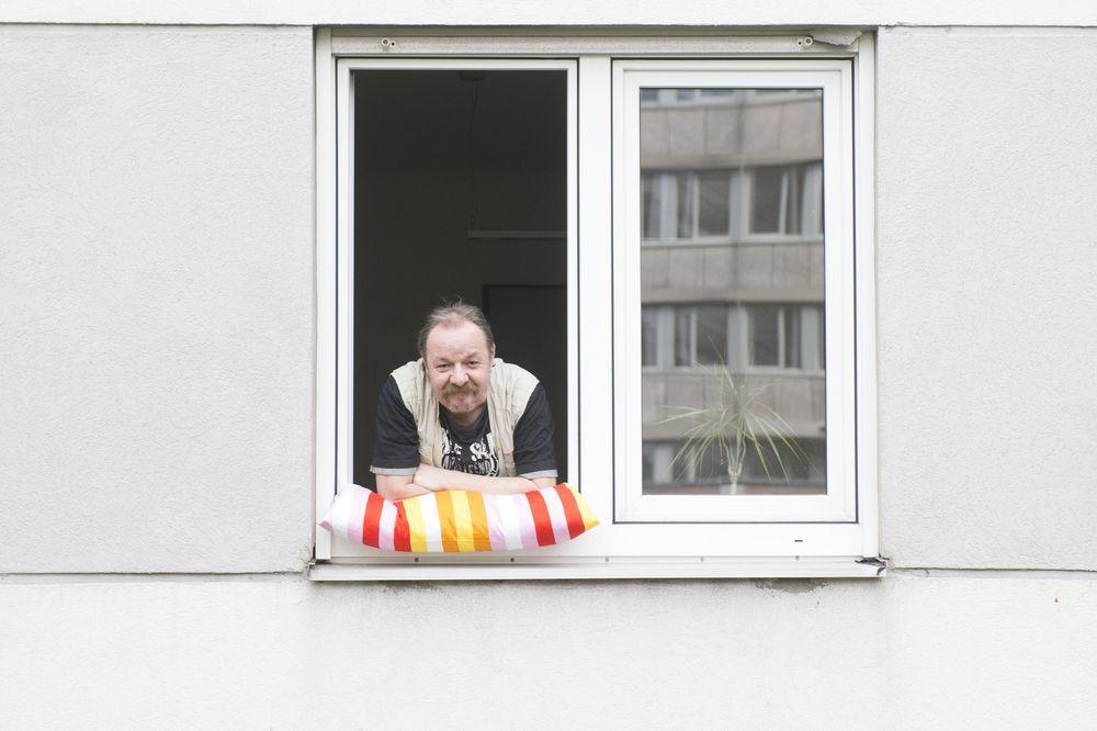 Ein Mann lehnt sich aus einem Fenster und stützt sich dabei auf einem bunten Kissen.