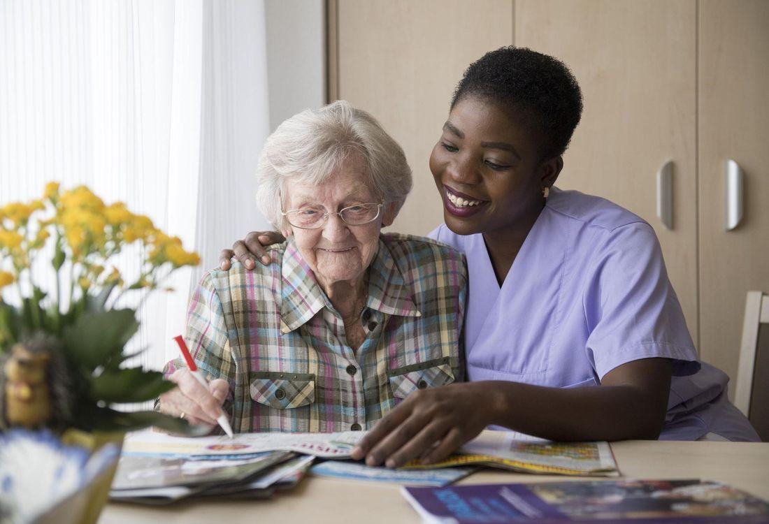 Eine Pflegerin und eine ältere Dame machen gemeinsam Kreuzworträtsel.