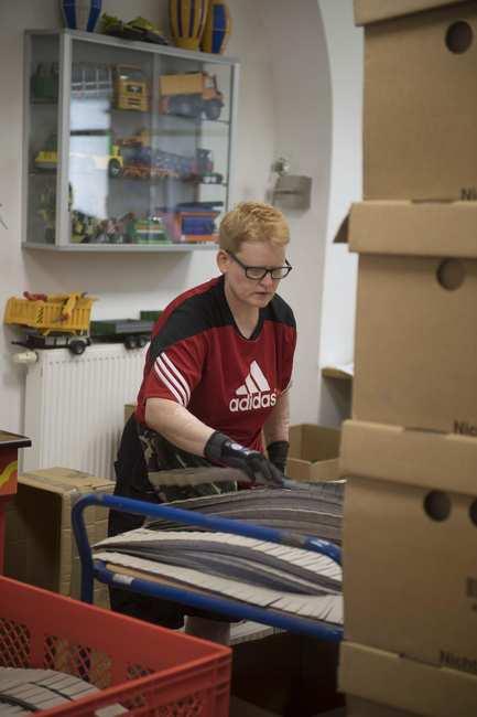 Eine Frau mit Brille, Arbeitshandschuhen und blonden kurzen Haaren steht an einem Werktisch. Vor ihr Kartons und verschiedene Kunststoffteile.