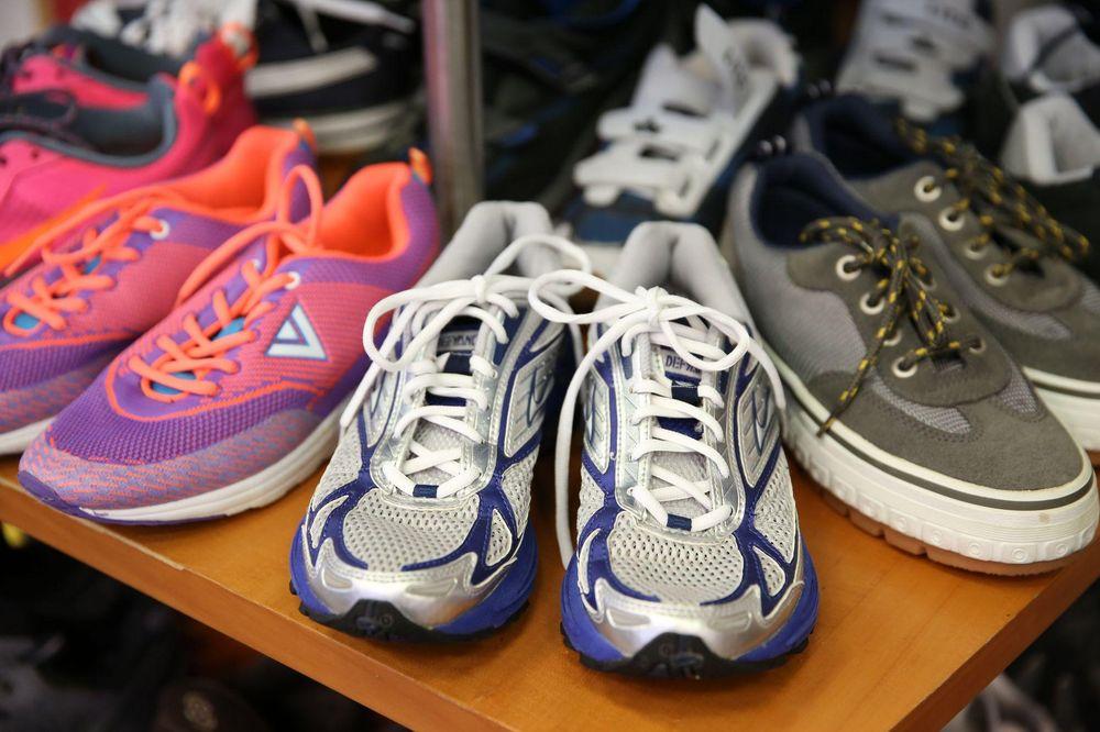 Auf einem Verkaufsregal stehen Sportschuhe und Sneaker gereiht.