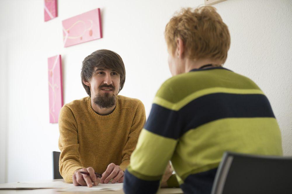 Ein Mann und eine Frau sitzen an einem Tisch. Der Mann im orange-farbenen Pullover berät die Frau im gestreiften Pullover. Die Frau ist nur von hinten zu sehen.