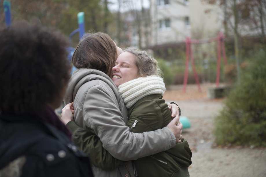 Zwei Mädchen umarmen sich. Sie lächeln.