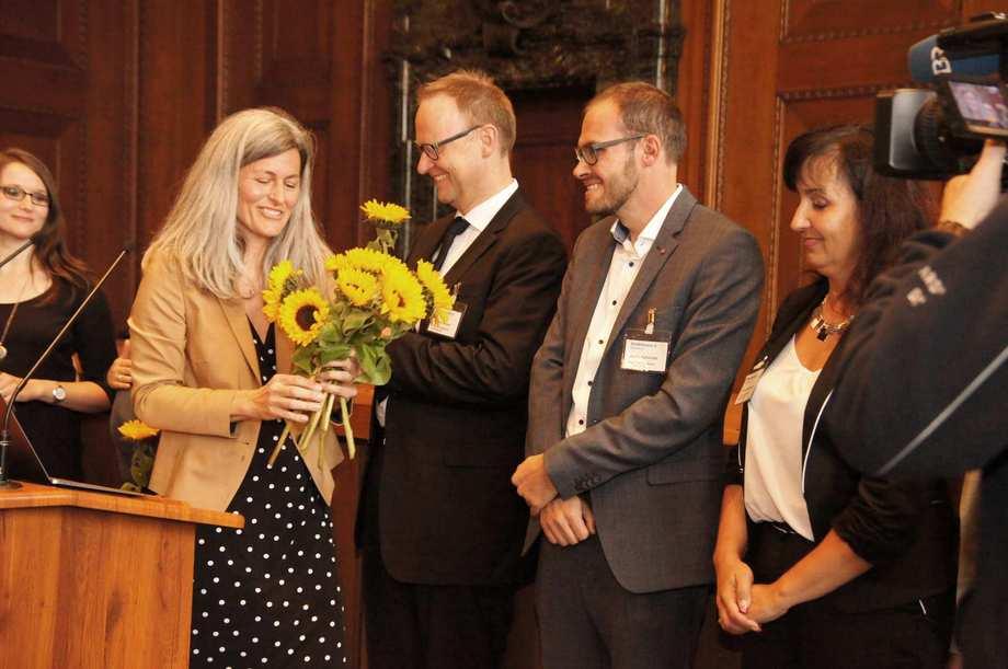 Eine Frau hält einen Strauß Sonnenblumen in der Hand. Sie verteilt diese an vier weitere Personen, die lächelnd vor ihr stehen.