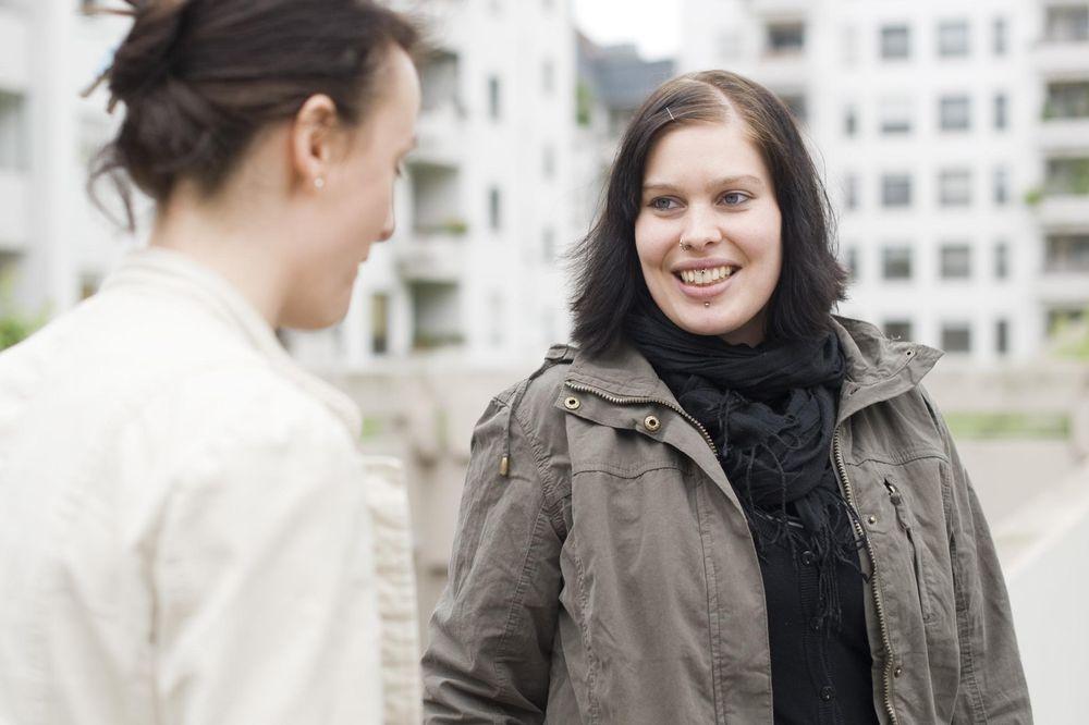 Zwei Frauen die sich gegenüber stehen und sich unterhalten.