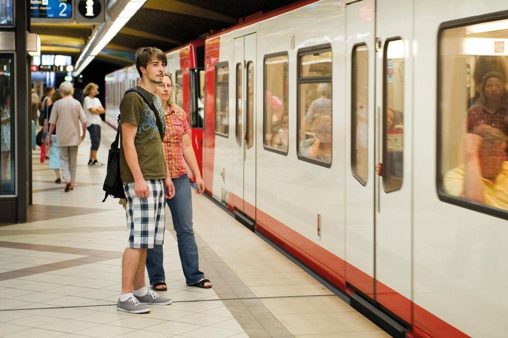 Zwei Personen stehen vor einer U-Bahn.