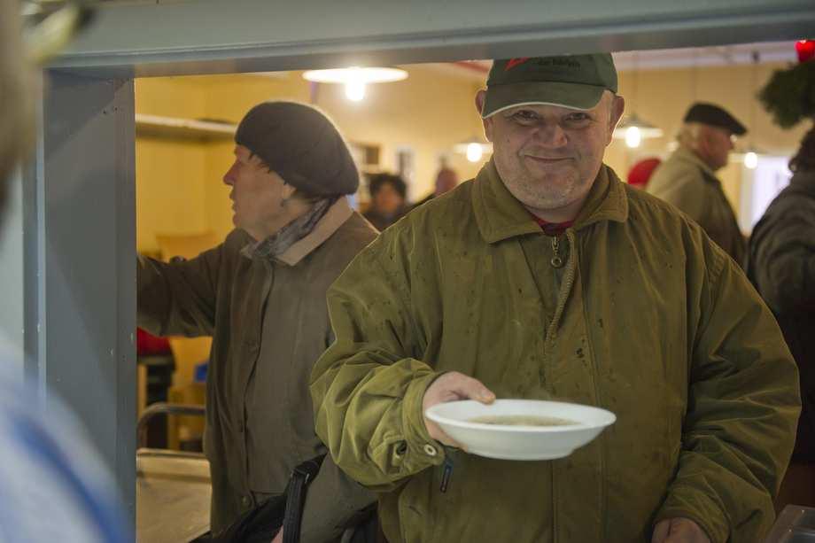 Ein Mann steht lächelnd an einer Theke. Er hat einen Teller Suppe in seiner Hand.