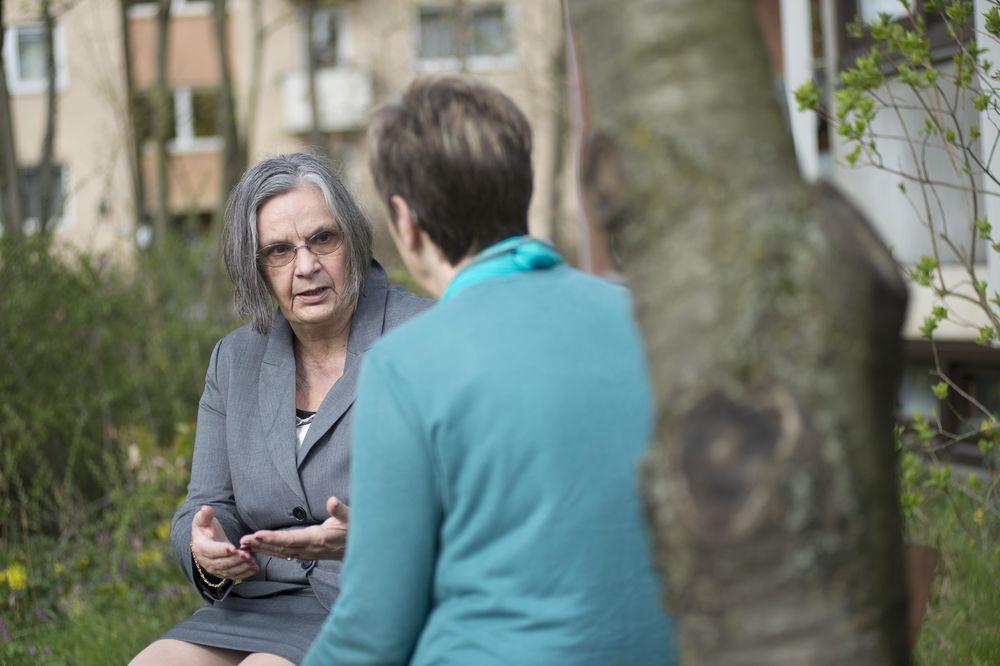 Zwei Frauen sitzen auf einer Bank im Grünen. Die eine erklärt der anderen etwas.