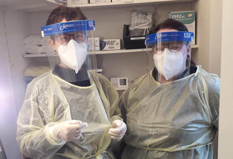 Zwei Frauen nebeneinander in Schutzanzügen, mit Masken, Handschuhen und Gesichtsvisieren.