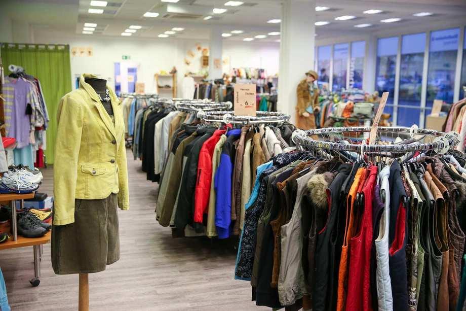 In einem großen Ladenraum stehen voll bestückte Kliederständer voller Jacken und Pullover. Im Vordergrund steht eine Kleiderpuppe.