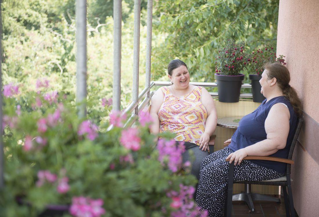 Zwei Frauen sitzen auf einem Balkon und unterhalten sich.