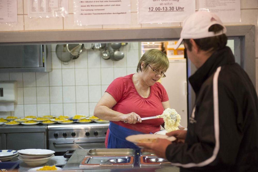 Ein Mann steht an der Essensausgabe und erhält von der Dame hinter der Theke eine Portion Kartoffelbrei.